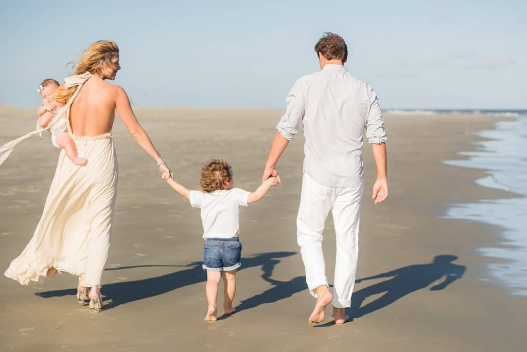 C'MON MAMA family photo holding hands on the beach