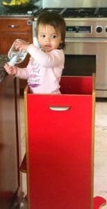 Little girl standing in the best baby gear Little Helper Kitchen Tower