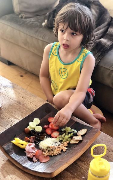 kid eating off of kid charcuterie board